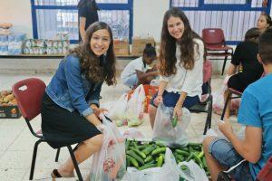 בנות חיוך למשפחה בהכנסת שקיות ירקות